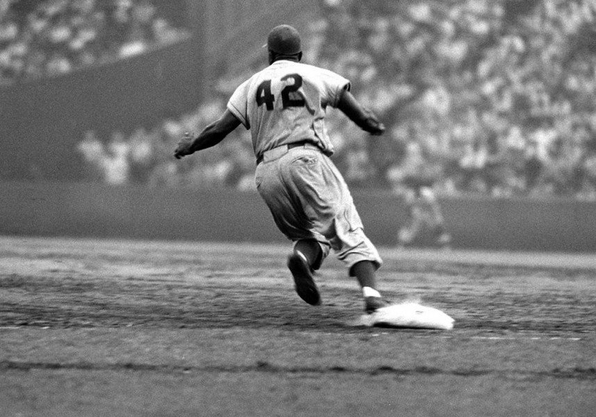 Jackie-Robinson-rounds-first-during-a-game-against-the-Giants-in-1956.